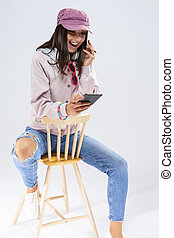 Funny Laughing Caucasian Brunette Girl With Smartphone and a Pair of Big Headphones. Against White Background