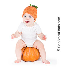 Funny laughing little baby sitting and playing on a huge pumpkin