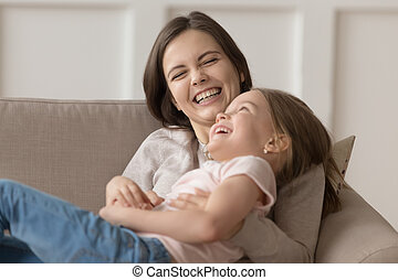 Funny laughing mother tickles little daughter family lying on couch