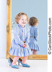 Funny laughing toddler girl with beautiful curly hair wearing a
