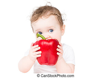 Funny little baby biting on a big red paprika