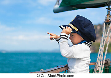 Funny little baby captain on board of sailing yacht watching...