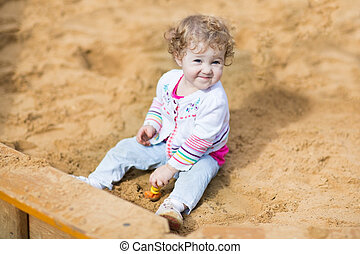 Funny little baby girl playing with sand on a playground