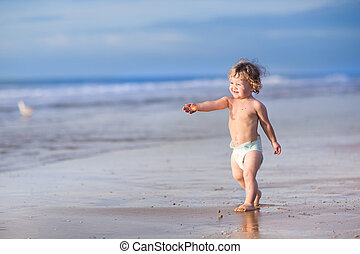 Funny little baby girl running on a beautiful tropical beach on