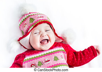 Funny little baby laughing and playing on a white blanket wearin