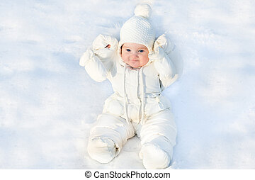 Funny little baby sitting in fresh snow wearing a white jacket a
