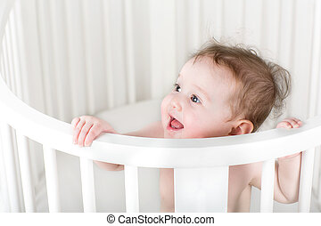 Funny little baby standing in a white round crib