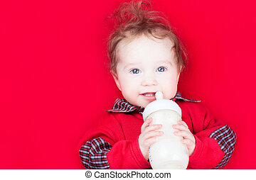 Funny little baby with a milk bottle