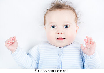 Funny little baby with blue eyes in a blue sweater