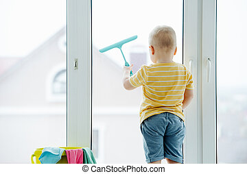 Funny little blond toddler boy is cleaning plastic window door with scrubber