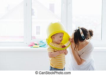 Funny little blond toddler boy is wearing big plastic bucket