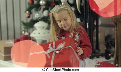 Funny little blonde girl with long hair sitting near a beautifully decorated Christmas tree and examines a big box with a gift