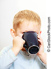 Funny little boy child drinking tea. Indoor