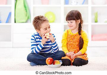 Funny little boy eating apple