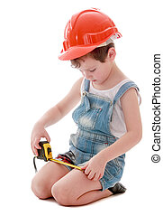 Funny little boy in denim overalls and a hard hat is considering