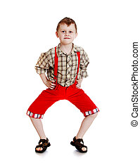 Funny little boy in red shorts with suspenders
