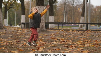 funny little boy is running in park area at autumn day, having fun at walking at weekend, active rest of family