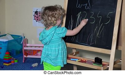 Funny little child cute blonde toddler girl drawing with chalk on black board