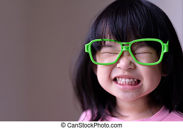 Funny little child with big green glasses