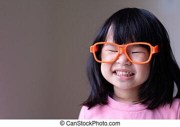 Funny little child with big orange glasses