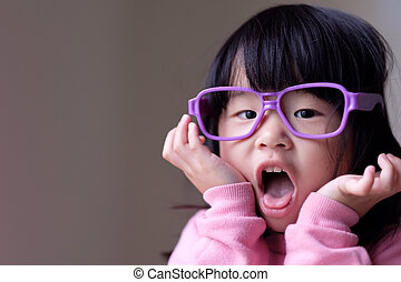 Funny little child with big purple glasses