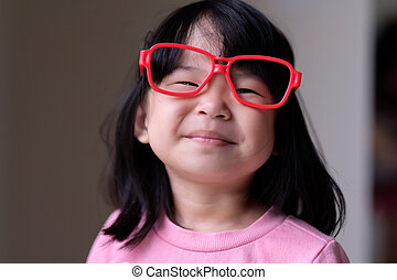 Funny little child with big red glasses