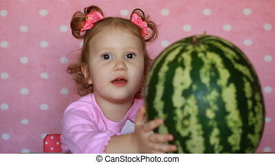 Funny little girl and big watermelon.The child expresses...