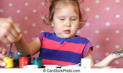 Funny little girl drawing gouache at a table on a pink background. Portrait of a cute baby with a brush and colored paints. Small artist. Creative concept. Childhood. Preschooler Education.