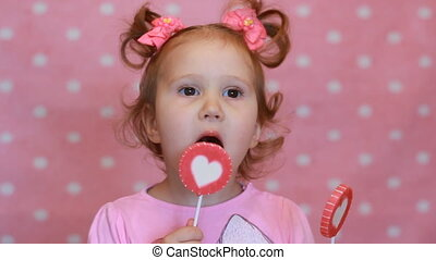 Funny little girl eating a candy with a picture of the heart. A happy cute baby holds a candy in his hand and expresses different emotions. The concept of love and childhood.