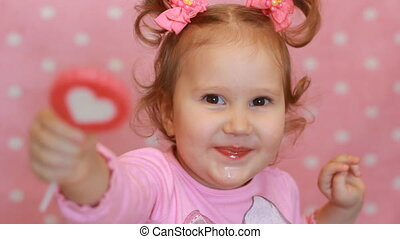Funny little girl eating a candy with a picture of the...