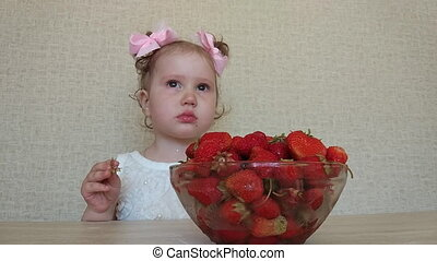 little girl eats a ripe strawberry