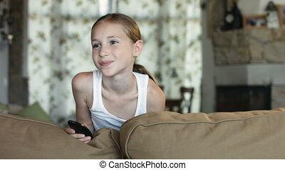 Funny little girl holding remote control smiling and...