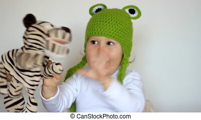 Funny little girl in green hats smiling, playing with toy and laughing. Cute happy smiling child and creative game in the form of toys on the hand. Tickling and laughter. Children's games.