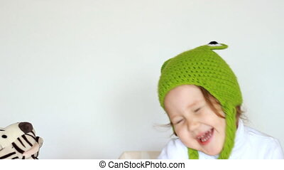 Funny little girl in green hats smiling, playing with toy and laughing. Cute happy smiling child and creative play in the form of toys on hand, close-up portrait. Games for children