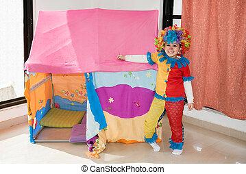 Funny little girl in multicolored clown wig costume.
