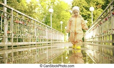 Funny little girl in orange waterproof raincoat and rubber...