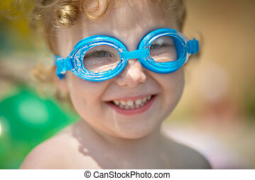 Funny little girl in water glasses