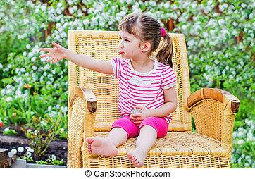 funny little girl in wicker chair