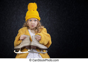 Funny little girl in winter clothes with skates.