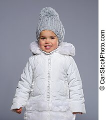 Funny little girl in winter coat isolated on grey