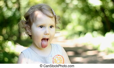 Funny little girl licks lollipop. A child on the nature in the park sits and eats an orange candy. Close-up