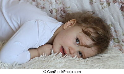 Funny little girl lying in bed smiling