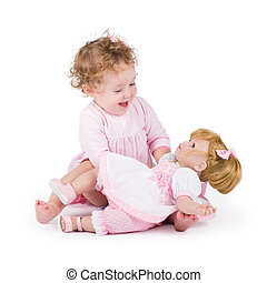 Funny little girl playing with a beautiful doll
