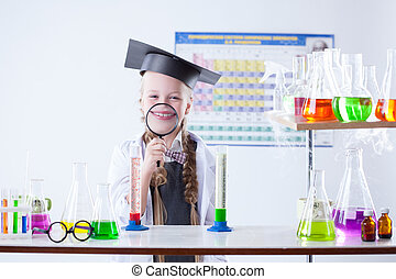 Funny little girl posing with magnifier in lab