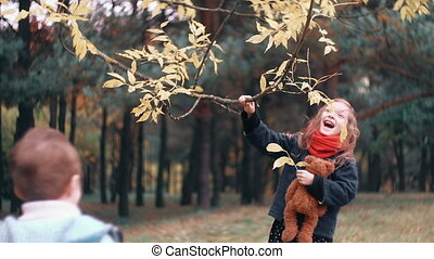 funny little girl shakes branch of tree and yellow autumn...
