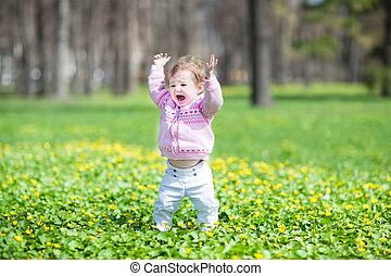 Funny little girl walking in a sunny park