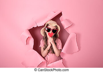 funny little girl with a heart on a stick on a colored background
