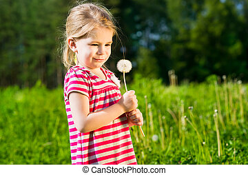 Funny little girl with dandelion in her hands makes wish