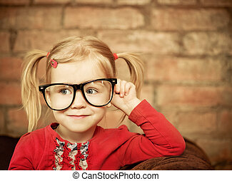 Funny little girl with glasses on brick wall background