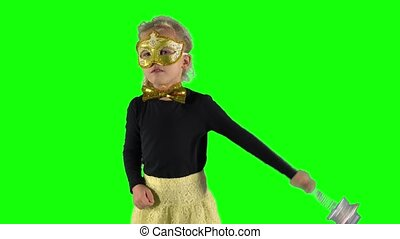 Funny little girl with mask and magic wand telling spell. ...